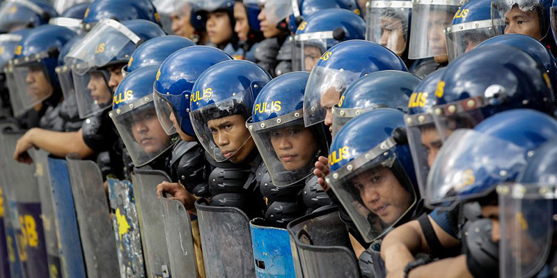 epa05605110 Filipino anti-riot police stand guard during a protest near the US Embassy in Manila, Philippines, 27 October 2016. Hundreds of protesters including Indigenous People, students and militant groups marched towards the US Embassy to protest against the presence of US military troops and condemning the violent dispersal on 19 October which left at least forty people hurt including twenty police officers and three people who were run over by a police van.  EPA/MARK R. CRISTINO